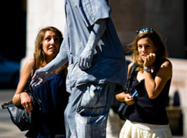 Two girls are frightened by street performer