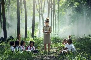 An asian teacher is educating her students in the forest