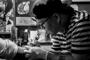 Tattoo Artist is working in his studio