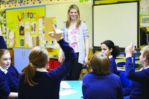 Teaching in front of her class and students are raising their hands